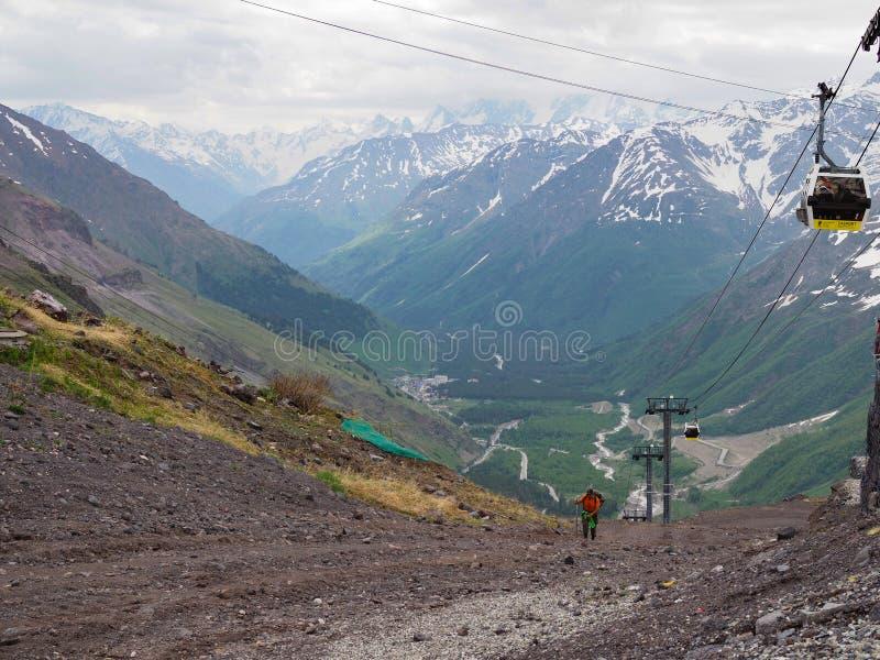 Ein älterer Mann klettert oben mit einem Wanderstock auf einem hohen Berg Konzept eines gesunden Lebensstils für ältere Leute Rus lizenzfreies stockbild