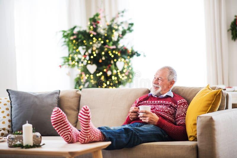 Ein älterer Mann mit dem Tasse Kaffee, der zu Hause auf einem Sofa zur Weihnachtszeit sitzt stockbilder
