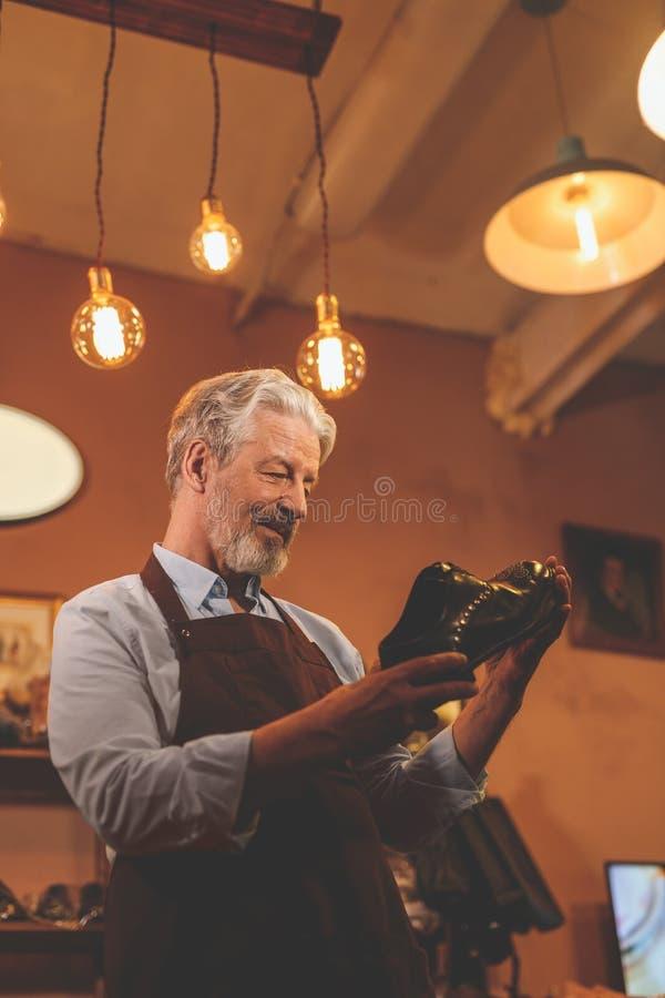 Ein älterer Mann mit einem Schuh I lizenzfreie stockbilder