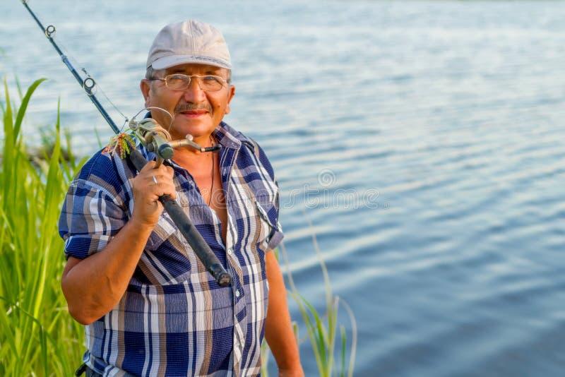 Ein älterer Mann mit einer Angelrute lizenzfreie stockfotos