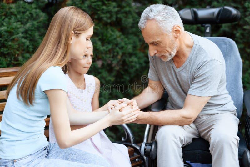Ein älterer Mann sitzt in einem Rollstuhl Er wird von einer Frau mit einem Mädchen gesehen Sie sitzen auf einer Bank im Park stockbilder