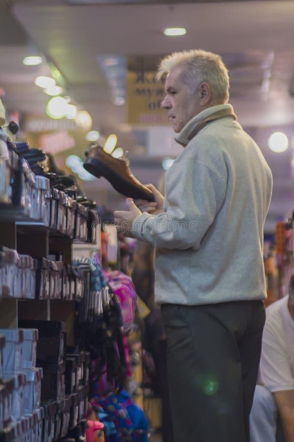 Ein älterer Mann wählt seine Schuhe im Speicher stockfotos