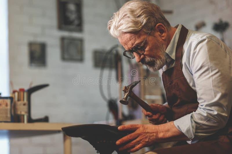 Ein älterer Schuster in der Uniform bei der Arbeit lizenzfreie stockbilder