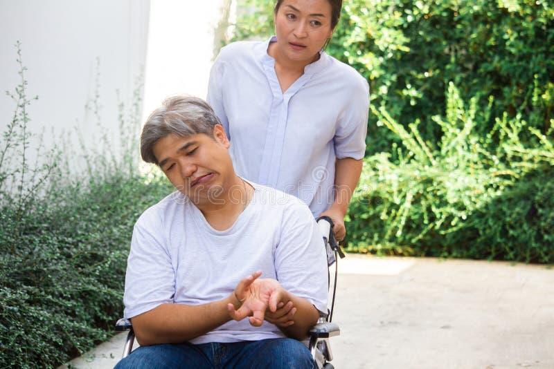Ein älteres Asien; midle - alterte Mann, den Patient auf einem Rollstuhl sitzen, seine Frau, Sorgfalt für ihn anzuwenden stockbilder