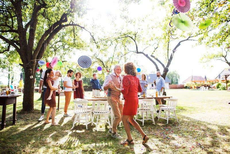 Ein älteres Paartanzen auf einem Gartenfest draußen im Hinterhof stockfoto