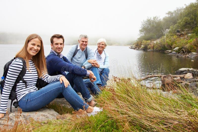 Ein älteres und junges erwachsenes Paar, das zusammen durch einen See sitzt stockfoto