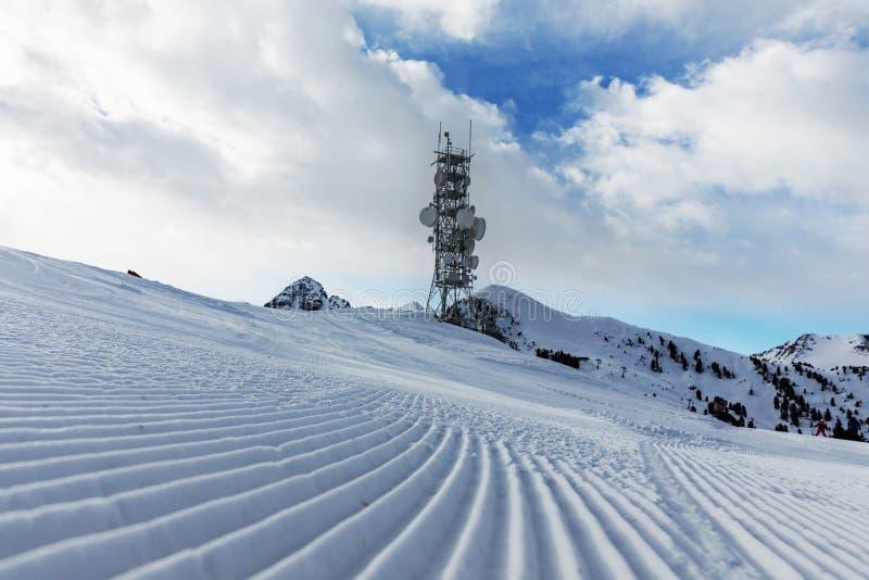 Ein Übermittler an der Spitze eines Berges im Dolomitskigebiet Leere Skisteigung im Winter an einem sonnigen Tag Bereiten Sie Ski stockbilder