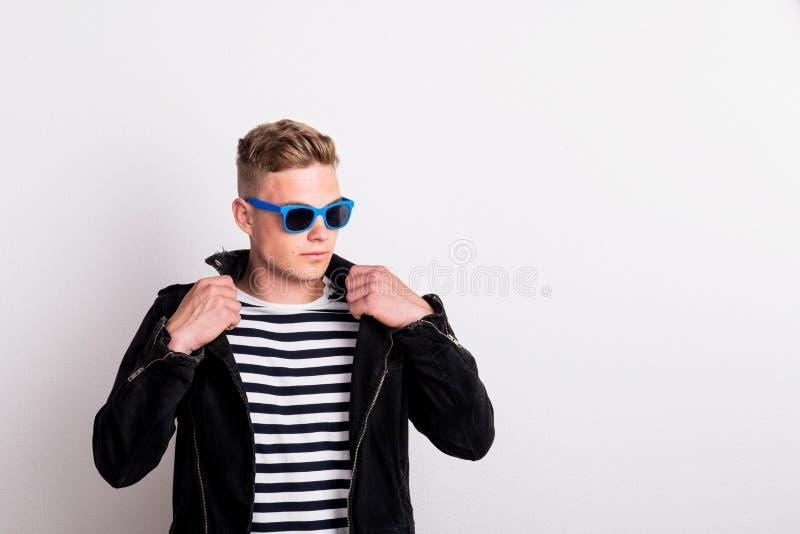 Ein überzeugter junger Mann mit blauer Sonnenbrille in einem Studio, tragendes gestreiftes T-Shirt stockfoto