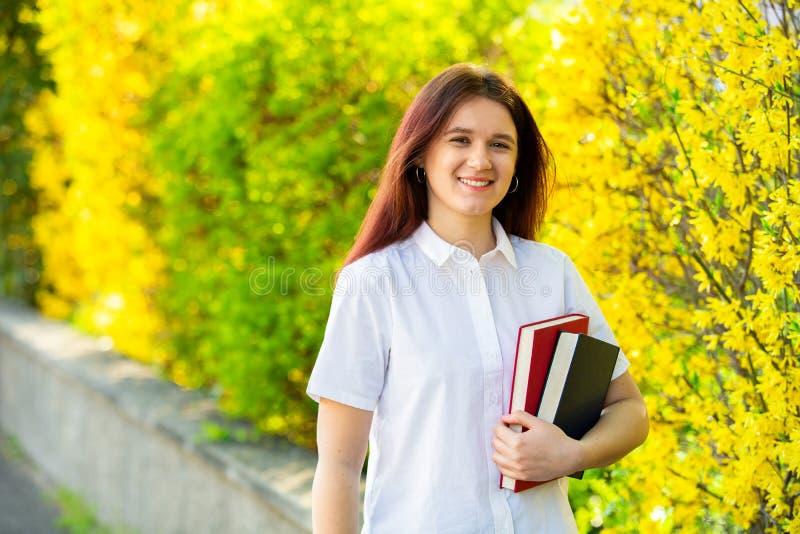 Ein überzeugter Student, der Bücher über Hochschulgebäudehintergrund hält stockbilder
