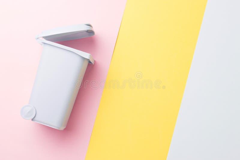 Ein Abfalleimer auf gelbem, rosa Hintergrund, Draufsicht, Konzept der Wiederverwertung stockbilder