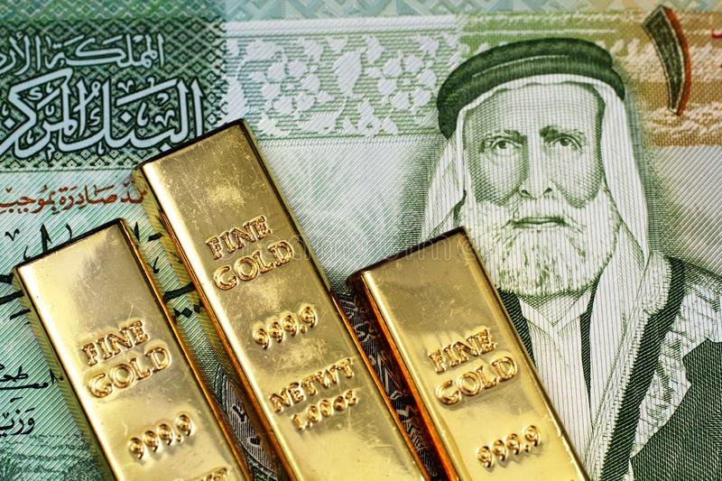 Ein Abschluss herauf Bild eines jordanischen Dinars mit kleinen Goldbarren stockfoto