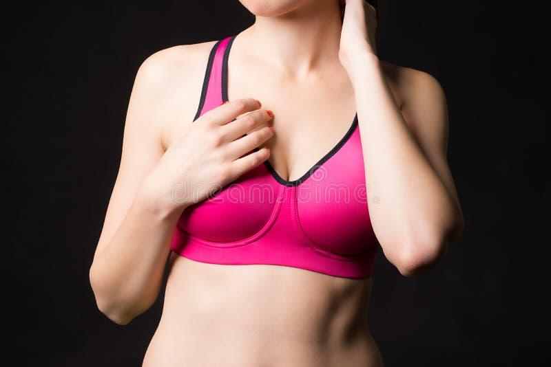 Ein Abschluss oben einer sportlichen Frau, die im rosa BH des Sports mit der netten Brust aufwirft lizenzfreie stockbilder