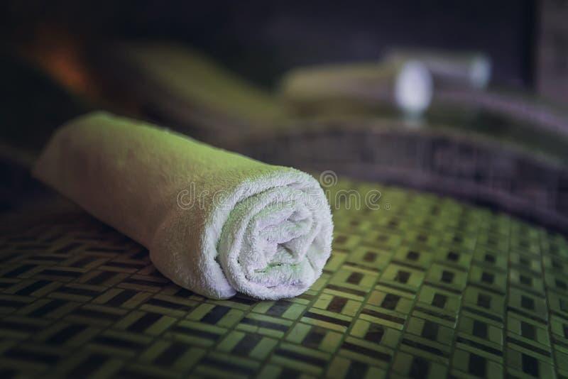 Ein Abschluss oben eines Baumwolle gerollten Badtuches auf dem hölzernen bedstone in einem Luxusbadekurort Saubere und neue einze stockbild