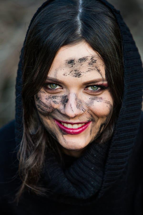 Ein Abschluss oben eines Frau ` s Gesichtes und der Hände umfasst im Schlamm Junge Frau mit schmutzigen Gesicht und den Armen auf lizenzfreie stockfotos