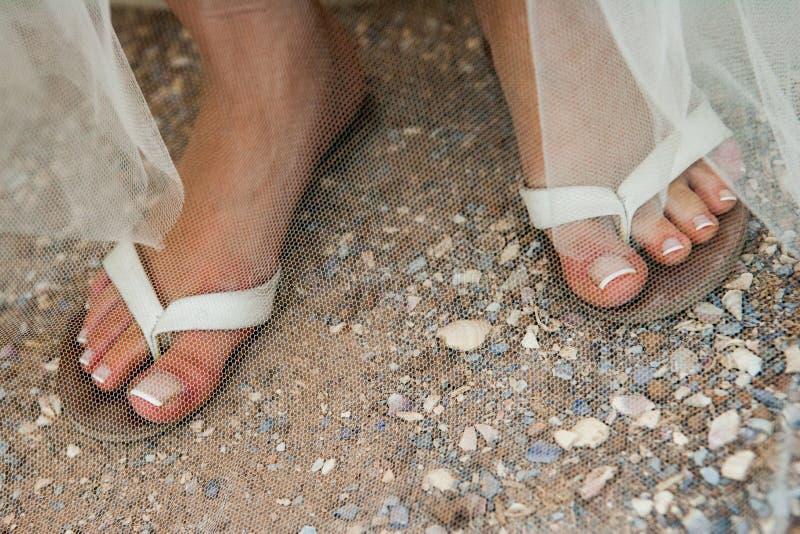 Ein Abschluss oben von Brautbeinen in den Flipflops auf einem Strand mit manikürten Nägeln stockfoto