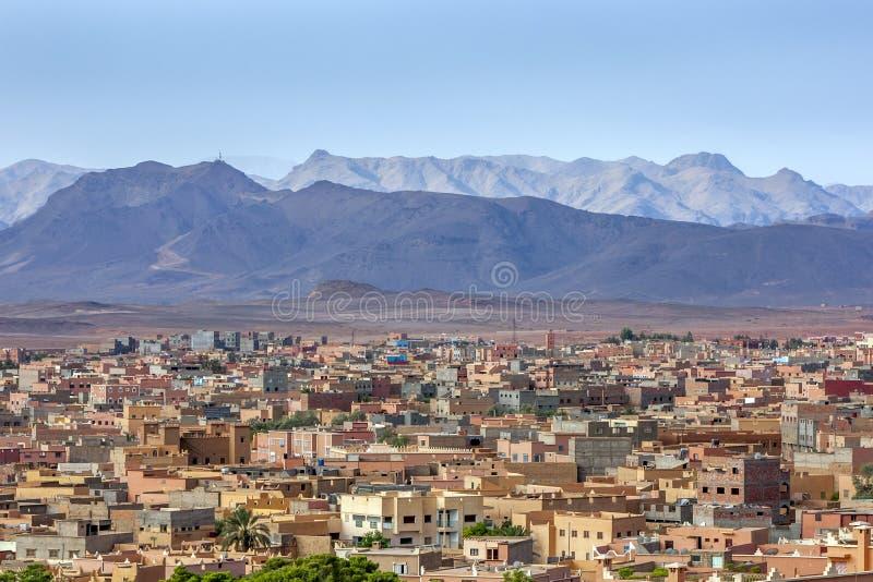 Ein Abschnitt des Dorfs von Tinerhir in Marokko mit den ausgezeichneten hohen Atlas-Bergen im Hintergrund lizenzfreie stockbilder