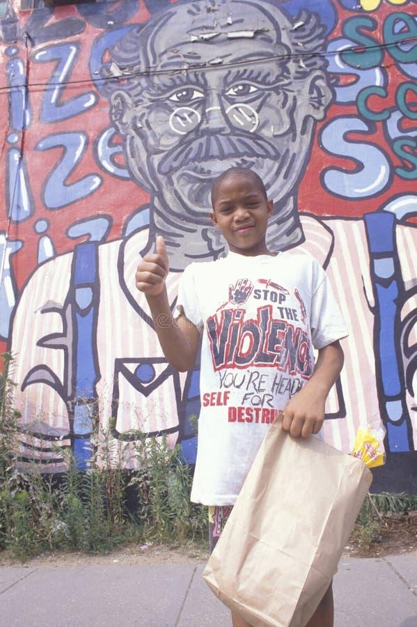 Ein African-Americanjunge vor einem Wandbild lizenzfreies stockfoto