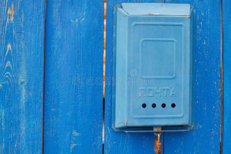 Ein alter blauer sowjetischer Briefkasten mit einer Aufschrift und einem rostigen Verschluss, die an einem l?ndlichen h?lzernen b stockbild