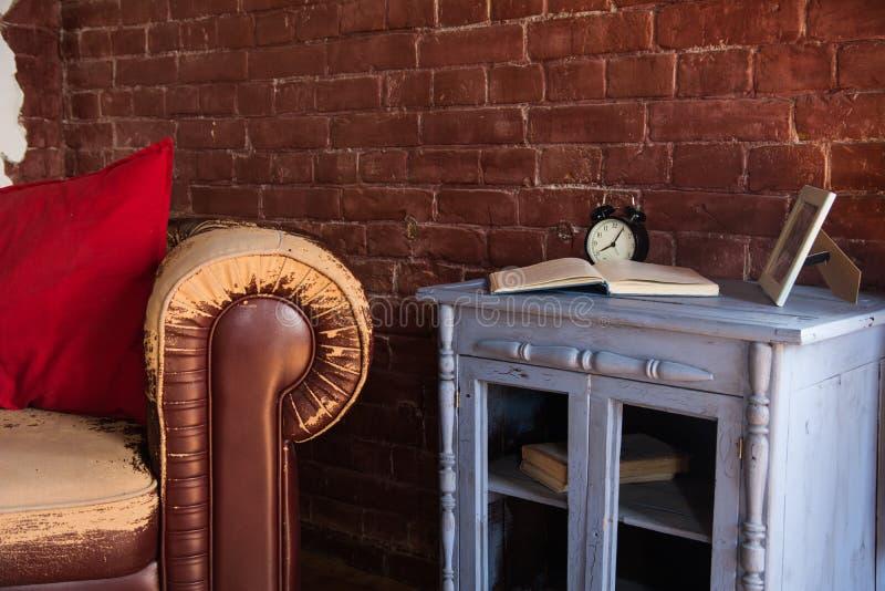 Ein alter brauner Lehnsessel und eine Uhr mit einem Buch auf einem hölzernen Buffet lizenzfreie stockfotografie