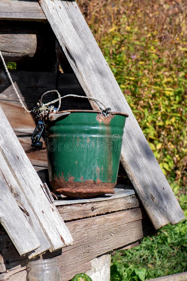 Ein alter Brunnen mit einem Eimer in einem europäischen Dorf stockbilder