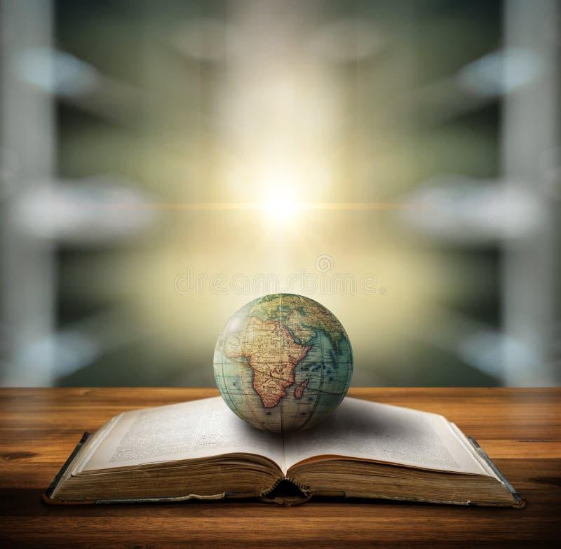 Ein alter Globus, der vor dem Hintergrund einer Bibliothek auf einem offenen Buch liegt Selektiver Fokus Retro-Stil Wissenschaft, lizenzfreie stockbilder