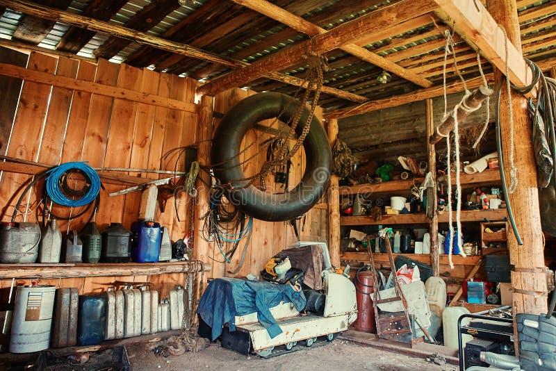 Ein alter Holzschuppen an einem abgelegenen Kasten, mit einem Reparaturwerkzeug, mit einer Gruppe alter Kanister und Zylindern fü lizenzfreie stockbilder