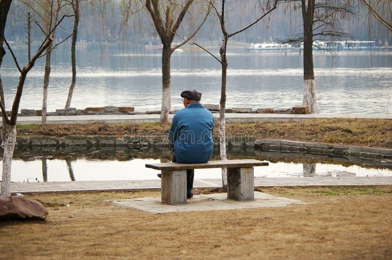 Ein alter Mann, der allein durch den See sitzt lizenzfreie stockfotos