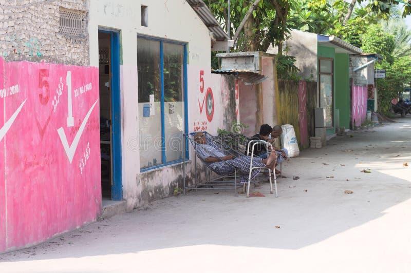 Ein alter Mann schläft in einer farbigen maledivischen Straße lizenzfreie stockbilder