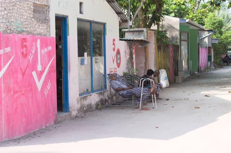 Ein alter Mann schläft in einer farbigen maledivischen Straße lizenzfreies stockfoto