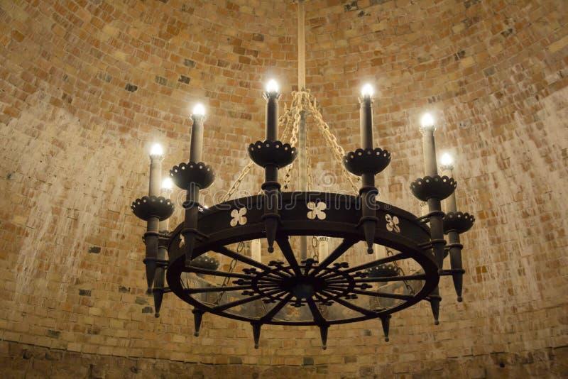 Ein alter Mittelalterleuchter auf einer Ziegelsteinschlossdecke stockfotografie