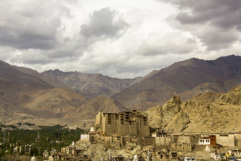 Ein alter tibetanischer Palast auf einer Klippe über der Stadt in einem Gebirgstal unter schwerem Himmel stockbilder
