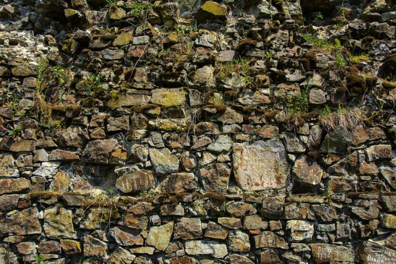 Ein alter verblaßter Stein in der gebrochenen verwitterten und zerbrochenen Wand O stockfotos