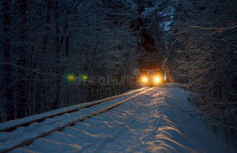 Ein alter Weinlesezug mit Wagen reitet durch einen schneebedeckten Wald des Winters lizenzfreie stockfotografie