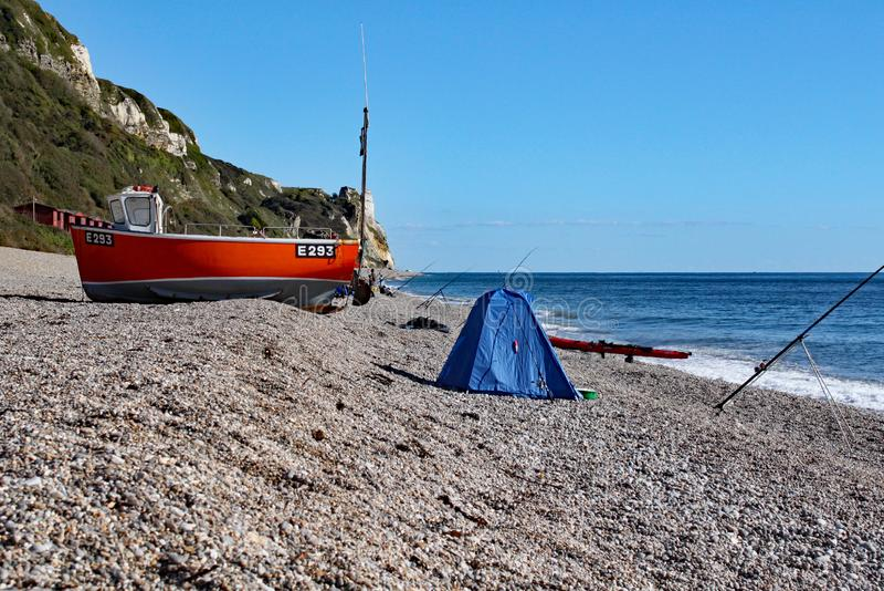 Ein altes Boot auf dem Strand bei Branscombe in Devon, England Die Ausrüstung der Fischer steht im Vordergrund stockfoto
