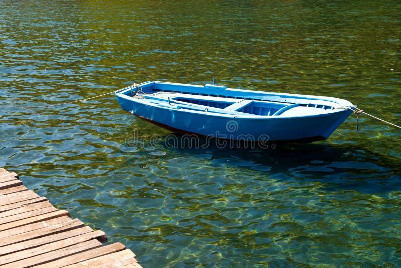 Ein altes Boot nahe einer Holzbrücke auf einem schönen See Fischerboot auf dem Pier lizenzfreies stockbild