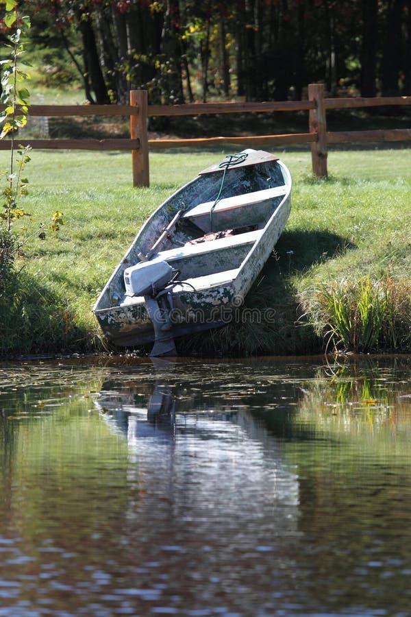 Ein altes Boot und ein Motor auf dem Ufer von einem See stockbild