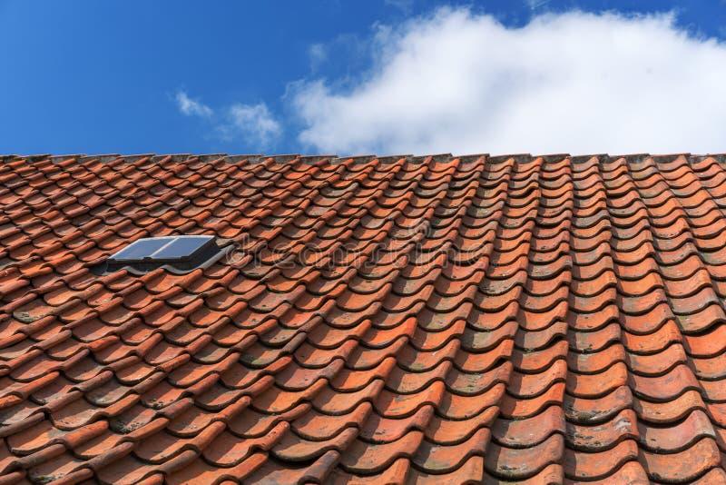 Ein altes Dach mit gebrannten Fliesen Dach im Dorfhaus gegen einen Hintergrund des blauen Himmels stockbild