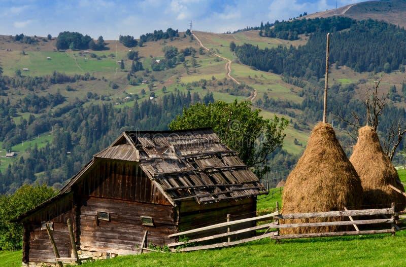 Ein altes farmer' s-Holzhaus steht auf einem Elefantberg nahe einem Heuschober gegen den Hintergrund von Bergspitzen lizenzfreie stockfotografie