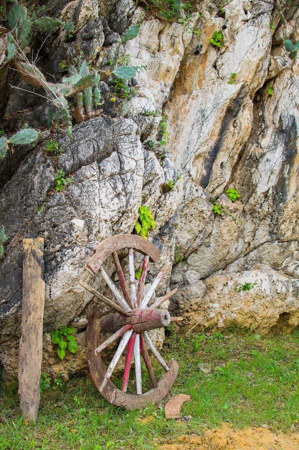 Ein altes gebrochenes hölzernes Rad des Lastwagens lehnend oben an einer Steinwand lizenzfreie stockfotos