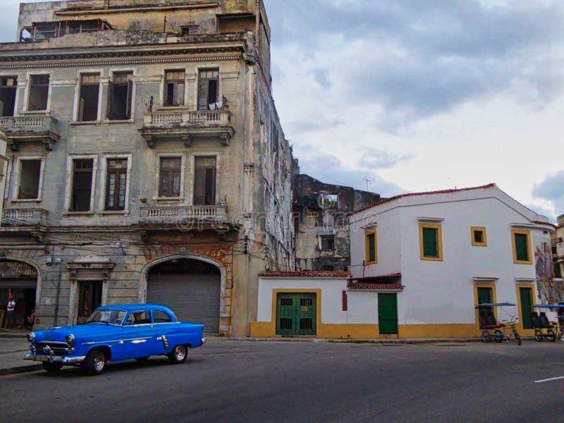 ein altes Haus in Kuba mit einem blauen Auto in der Front lizenzfreies stockfoto