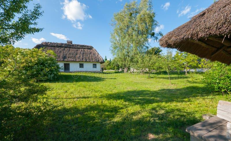 Ein altes Haus mit Strohdach auf einem grünen Rasen im Park lizenzfreie stockfotos