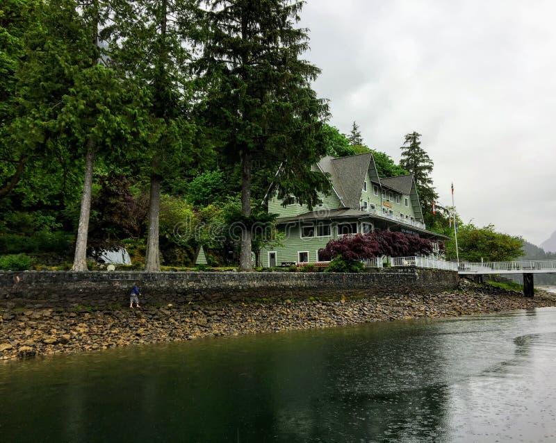 Ein altes Hotel neben dem Ozean umgeben durch hohe immergrüne Bäume im Britisch-Columbia, Kanada lizenzfreie stockfotografie