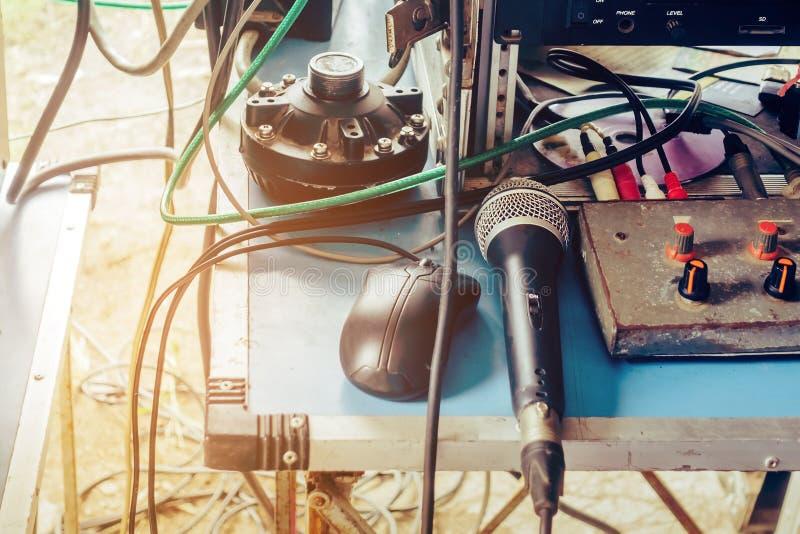 Ein altes Mikrofon mit schwarzem Kondensator und eine schwarze Maus, die auf einem Audiotabelle mit einem Kabel für den Einsatz i lizenzfreie stockfotografie