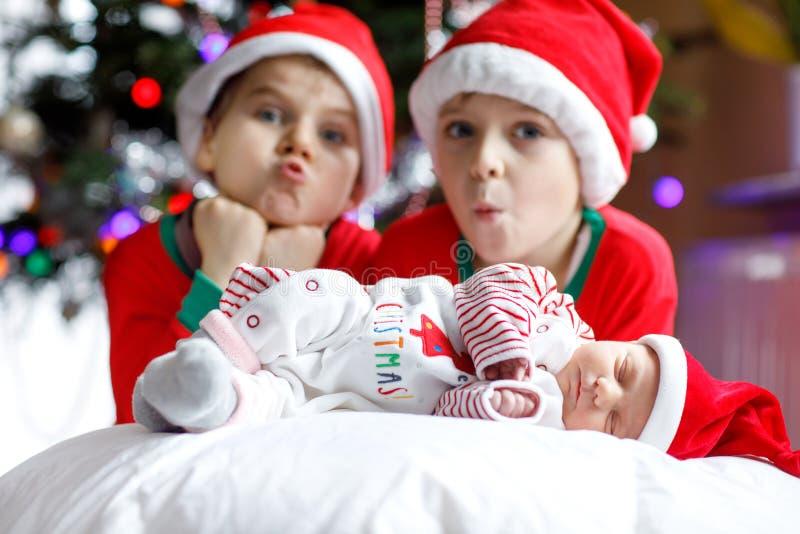 Ein altes neugeborenes Baby der Woche und zwei Geschwister scherzen Jungen in Santa Claus-Hüten nahe Weihnachtsbaum mit bunter Gi lizenzfreies stockfoto