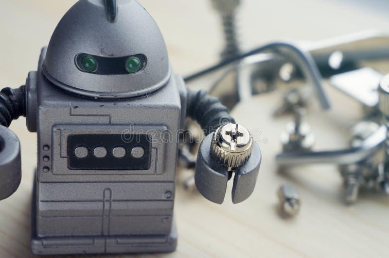 Ein altes Plastikroboterspielzeug, das eine kleine Schraube, Metallabfallkram auf dem unscharfen Hintergrund hält stockbilder