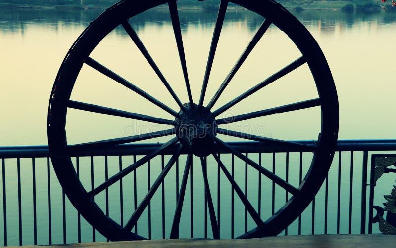 Ein altes Rad des Ochsenwagens zum Zaun an der Flussseite installieren stockfotos