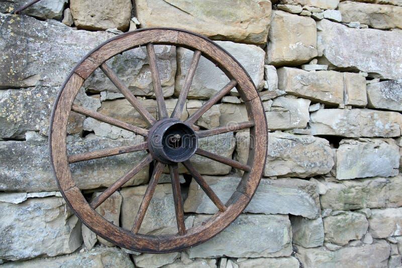 Ein altes Rad eines Lastwagens, der an einer Wand hergestellt von den Steinen hängt stockbild