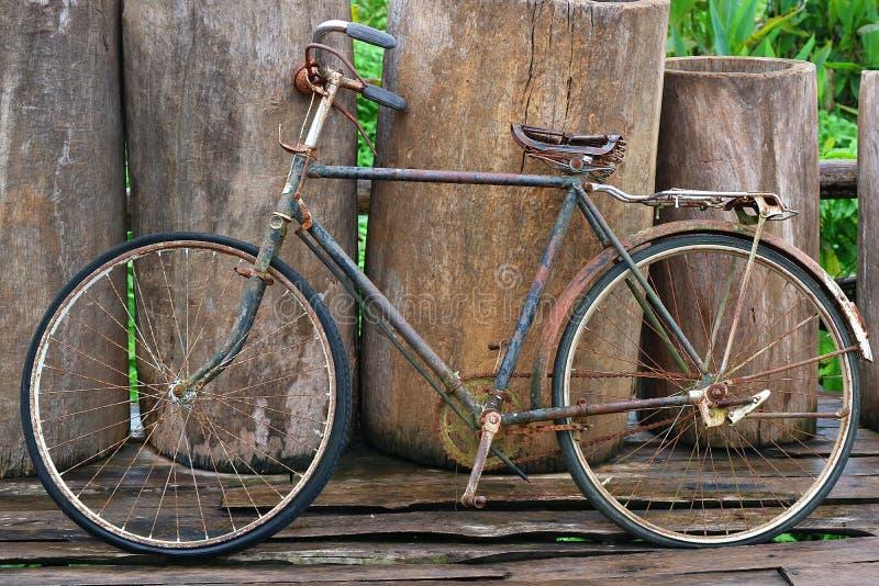 Ein altes Retro- antikes Weinlesefahrrad, das am Bretterzaun sich lehnt lizenzfreies stockbild
