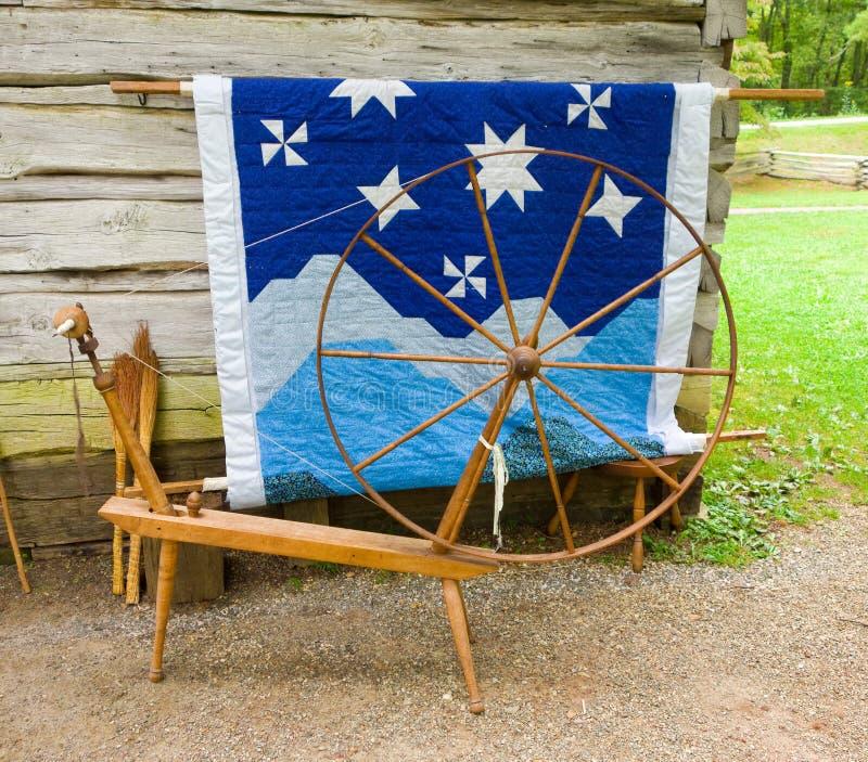 Ein altes Spinnrad und eine Steppdecke auf Anzeige an einer historischen Stätte in Virginia stockbilder