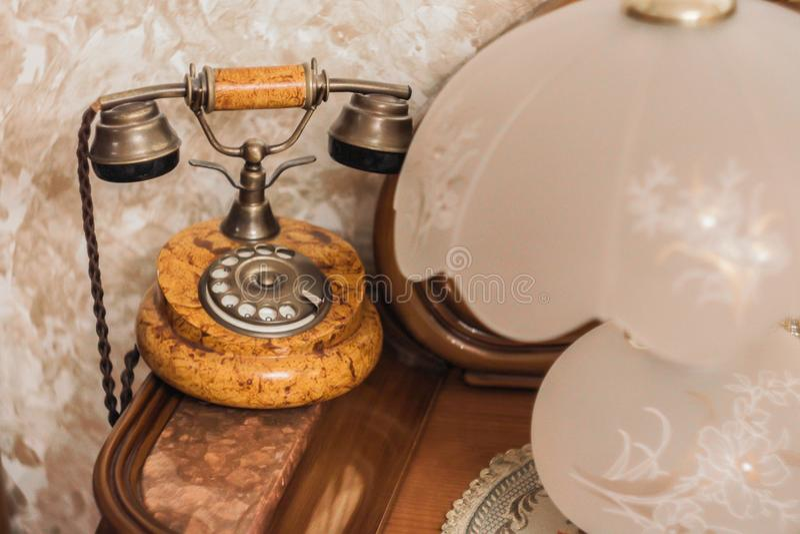 Ein altes Telefon und eine Lampe auf einem Holztisch stockfotografie